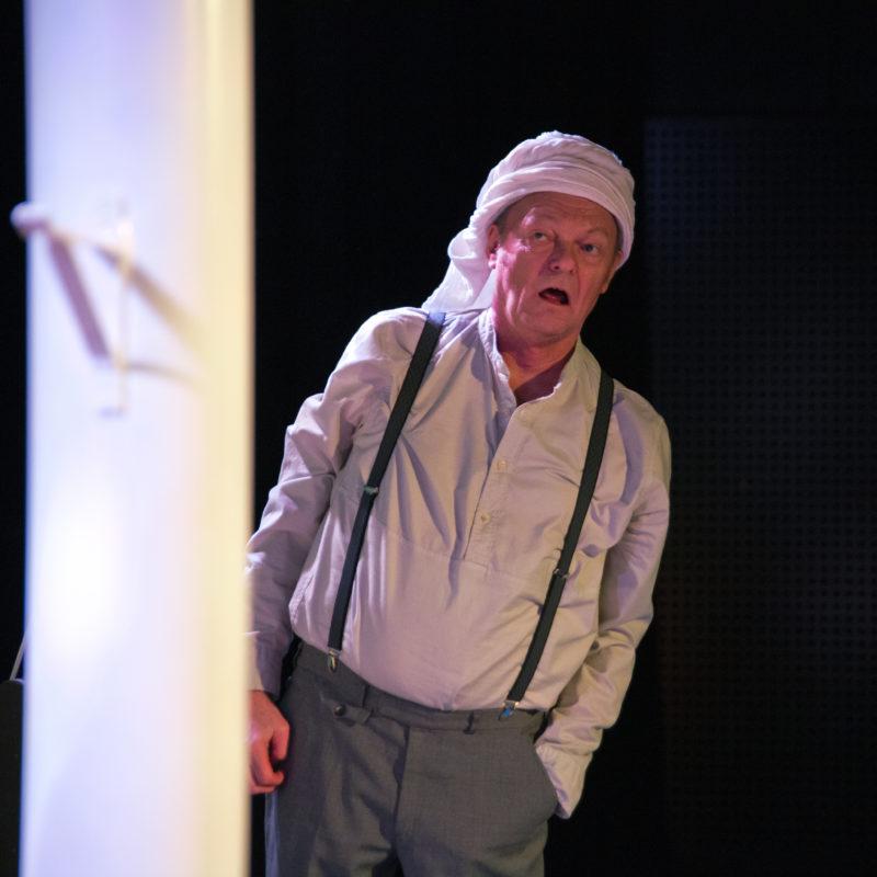 Mann med et hvitt sjal rundt hodet