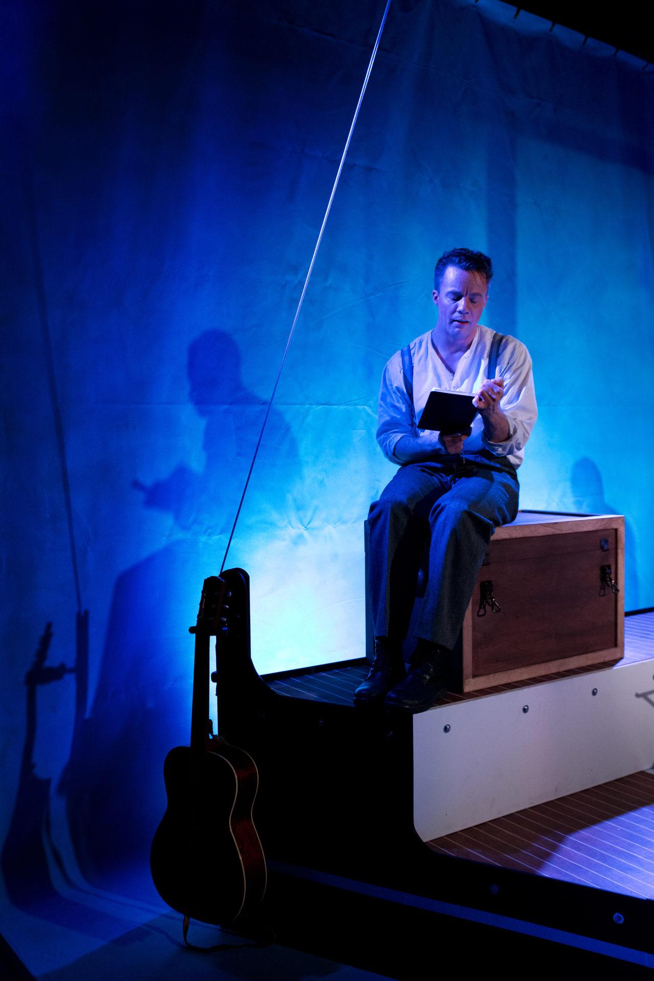 Mann leser fra bok på en båt