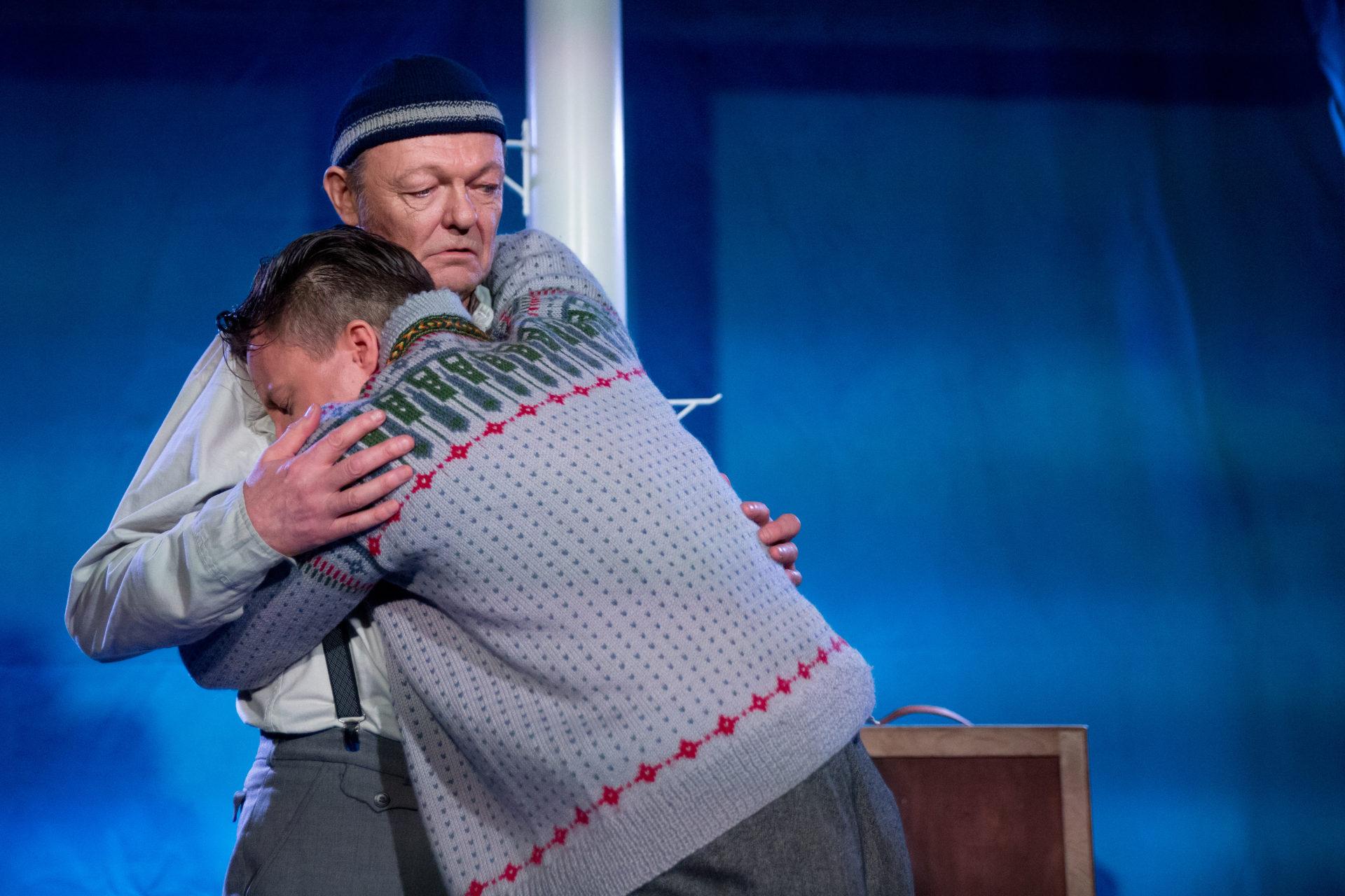 Mann gråter i armene til en annen mann