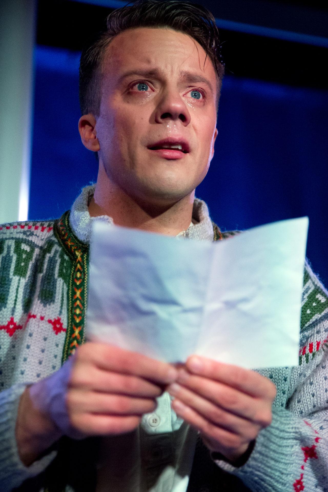 Mann gråter med et brev i hendene