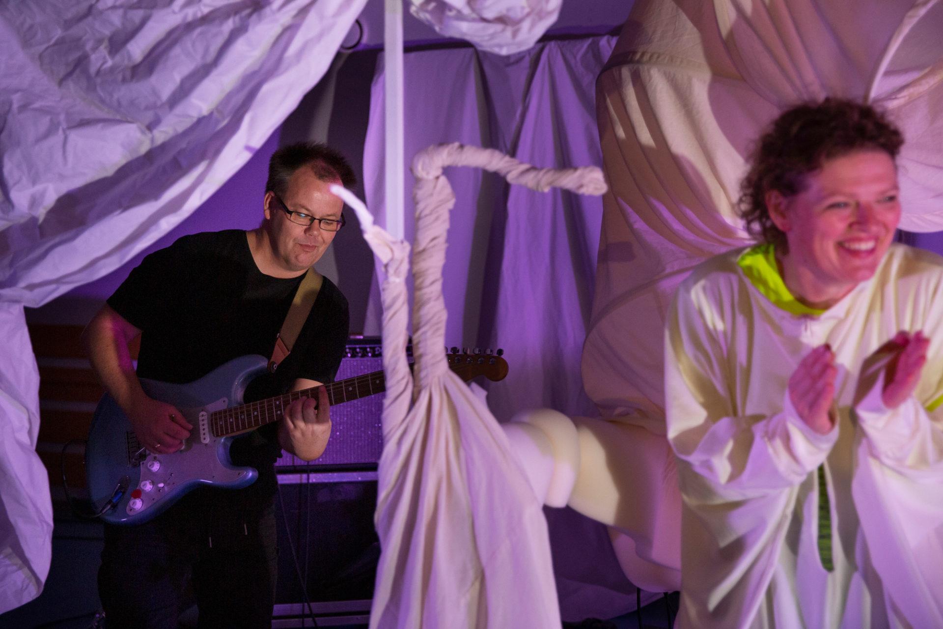Bilde av gitarist i bakgrunnen av skuespiller