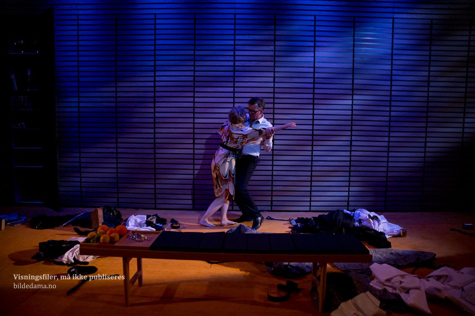 To personer danser i et rotete rom