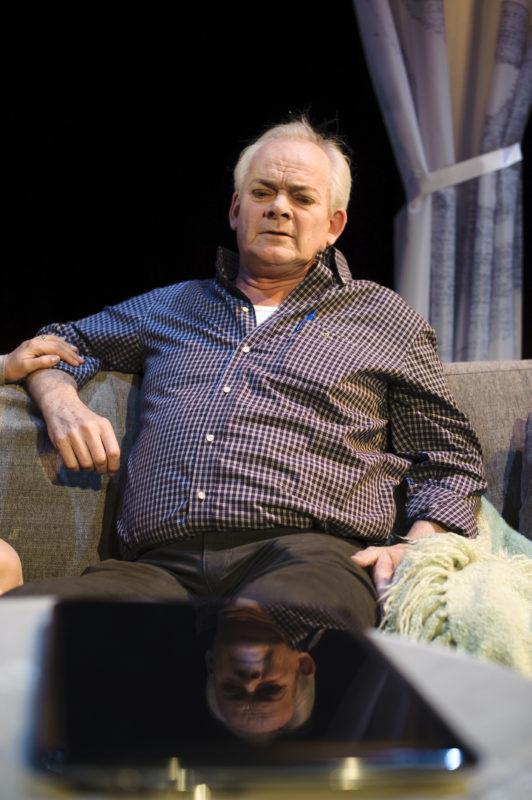 mann sitter på sofa
