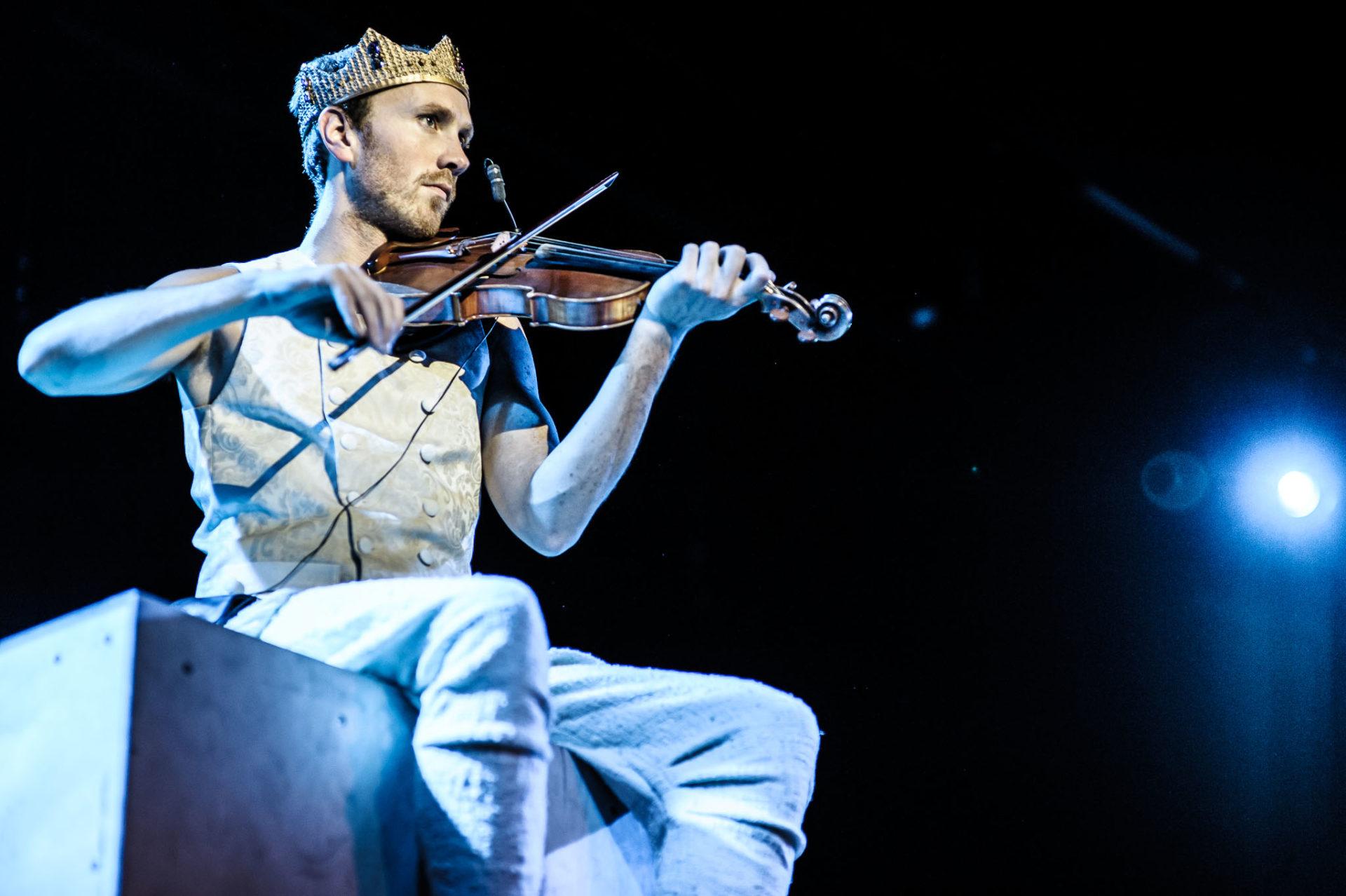 mann med krone spiller fiolin
