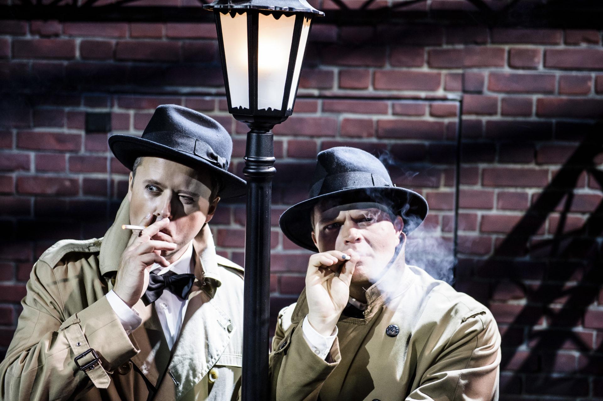 To menn røyker i frakk og hatt