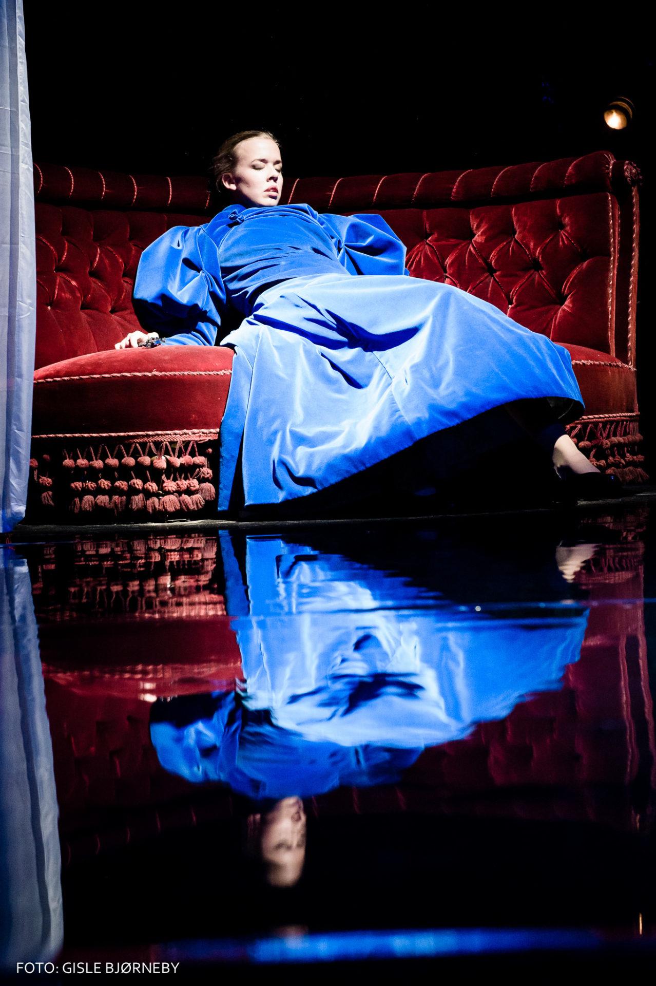 dame i blå kjole ligger på sofa