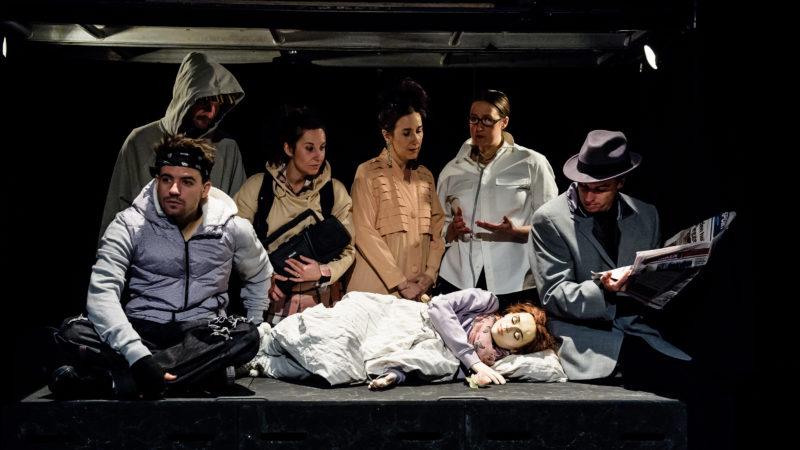 Gruppe mennesker står rundt sovende dukke