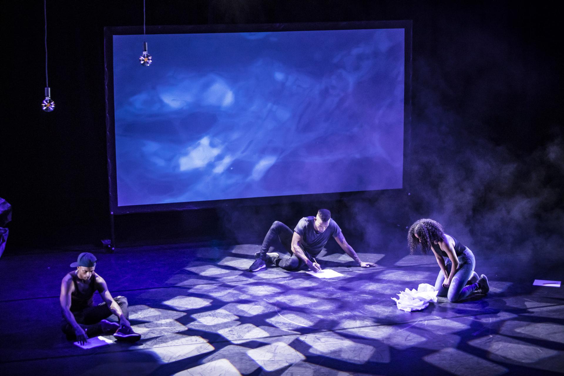 Tre personer sitter på gulvet med ark