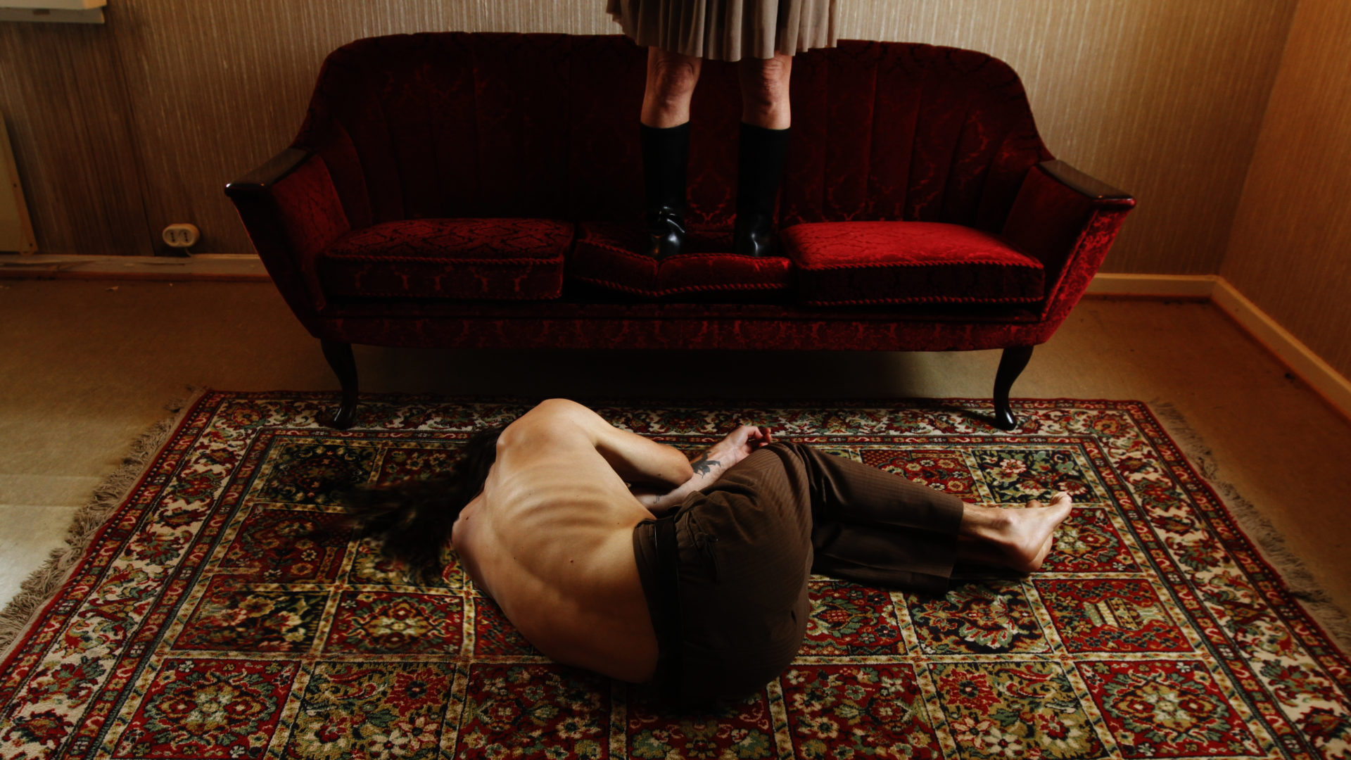Mann ligger på gulvet