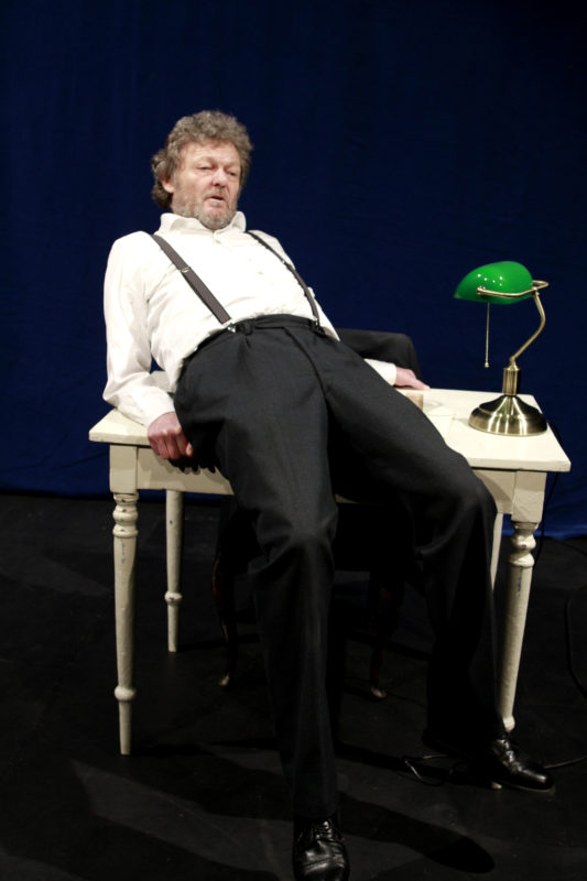 Mann lener seg på en pult