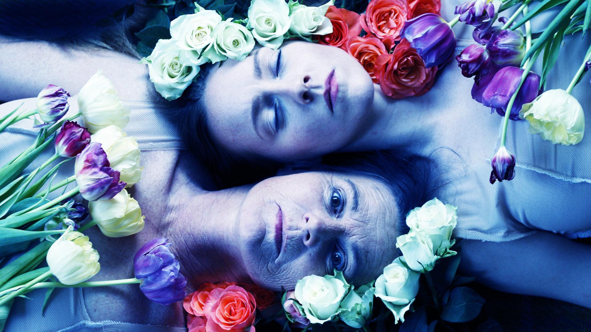 To damer som ligger på bakken omringet av blomster
