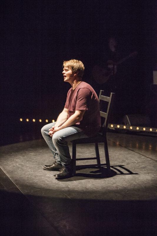 Mann sitter på en stol