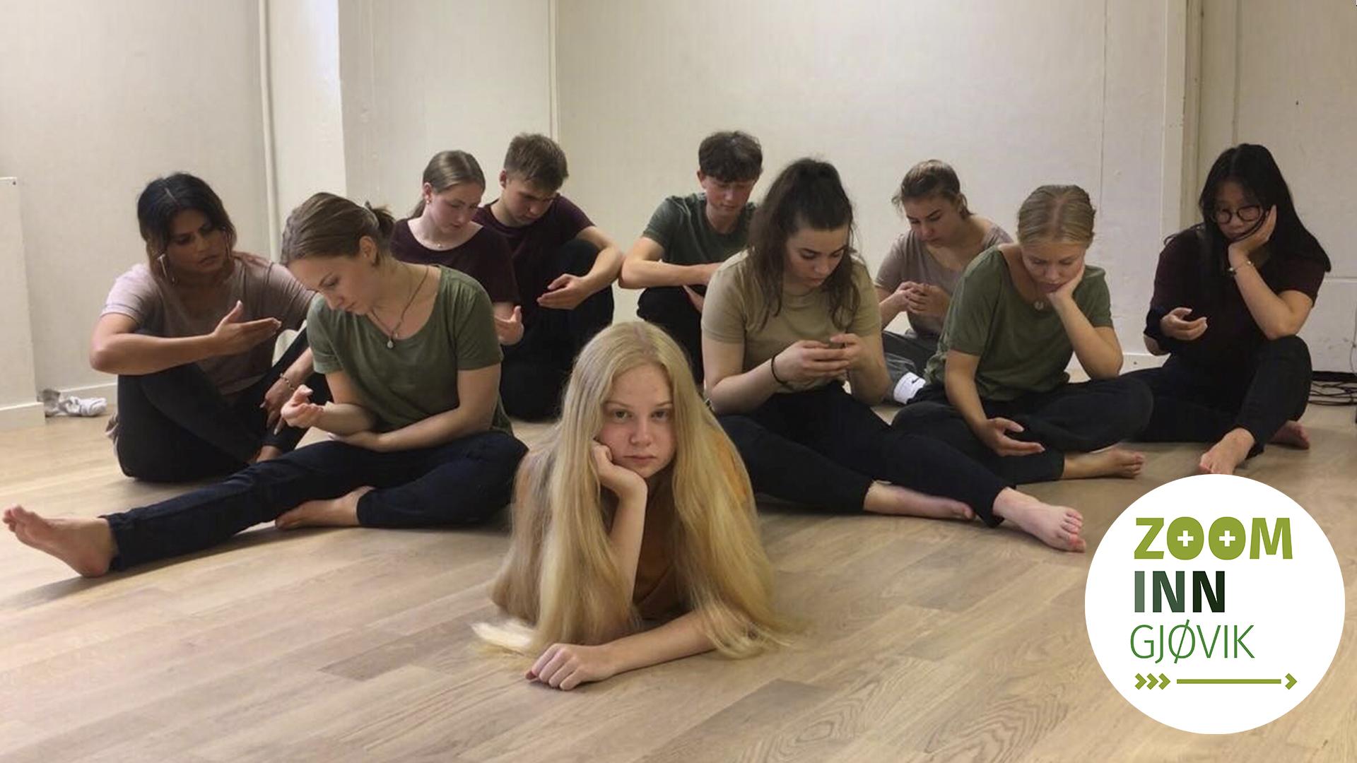 En gruppe ungdommer sitter på gulvet og ser på usynlige telefoner