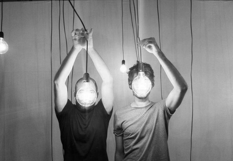 To menn med lyspærer foran ansiktene sine