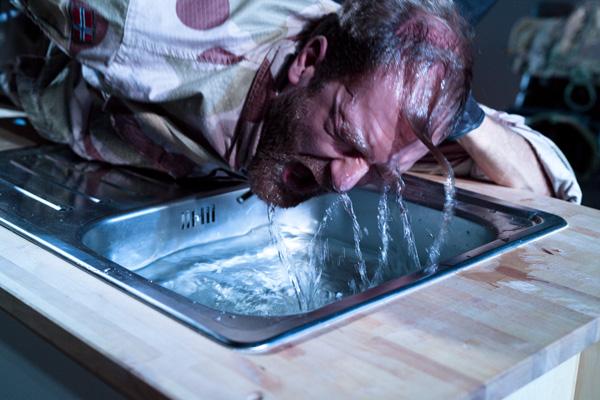 mann med hodet i vasken